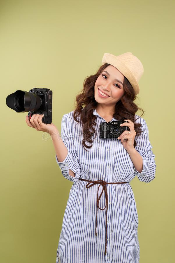 Young woman comparing professional and compact cameras on a solid background.  stock images