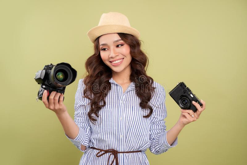 Young woman comparing professional and compact cameras on a solid background.  royalty free stock photos