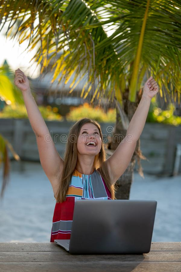 Young woman with computer in front of the palm royalty free stock image