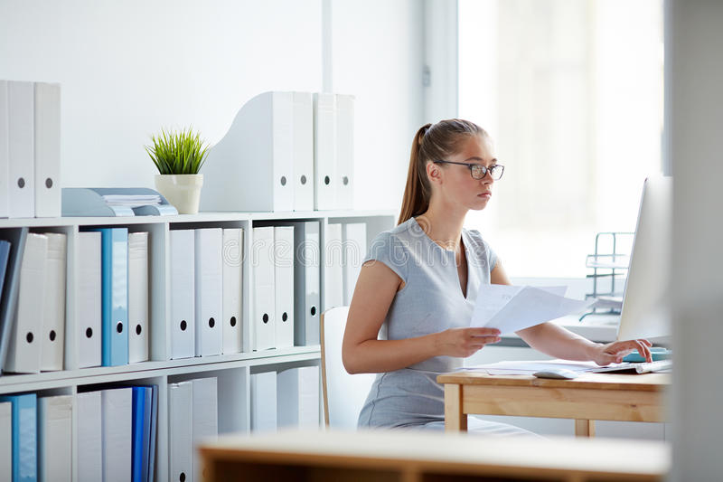 Young Woman Concentrated on Work. Young female office worker at computer desk sorting documentation and data alone in light spacious room royalty free stock photography