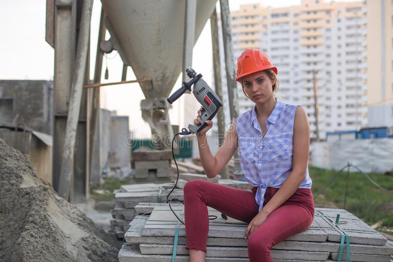 Young woman in construction helmet with drill sits on cement and concrete slabs on construction site near huge pile of sand stock images