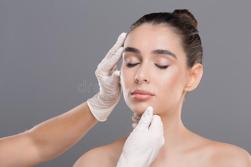 Young woman on consultation at beautician, grey background. Plastic surgery concept. Young woman on consultation at beautician, grey background stock photos
