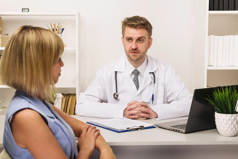 Young woman on a consultation with a male surgeon or therapist in his office royalty free stock photo