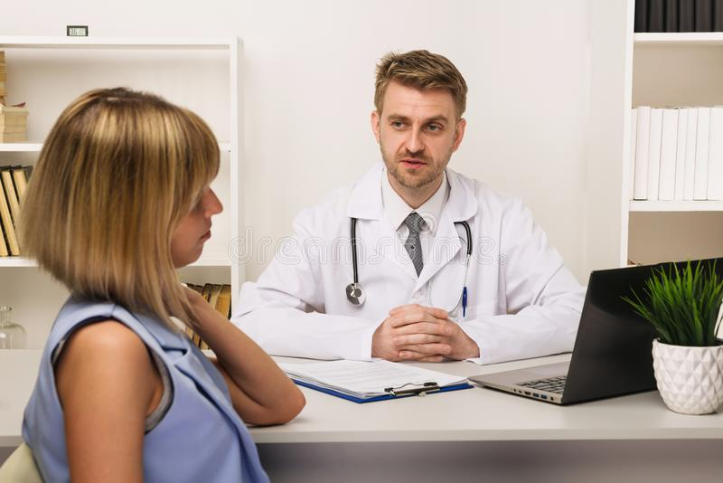 Young woman on a consultation with a male surgeon or therapist in his office stock images