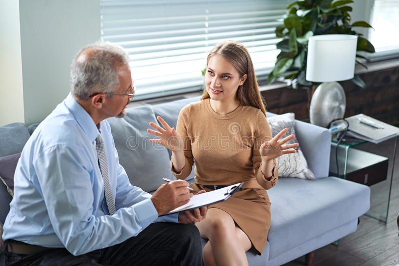 Young woman at a consultation with a psychotherapist. Psychologist having session with her patient in office, giving him stock photography