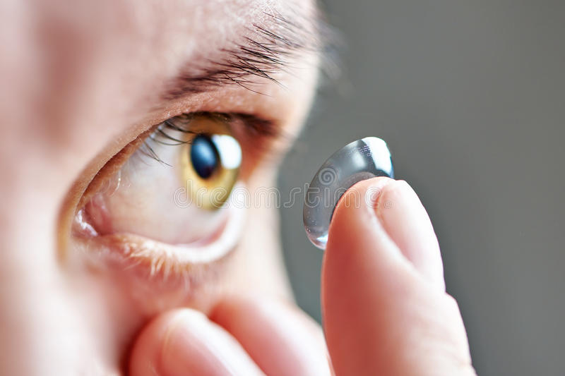 Young woman with contact lens. Medicine and vision - young woman with contact lens royalty free stock images
