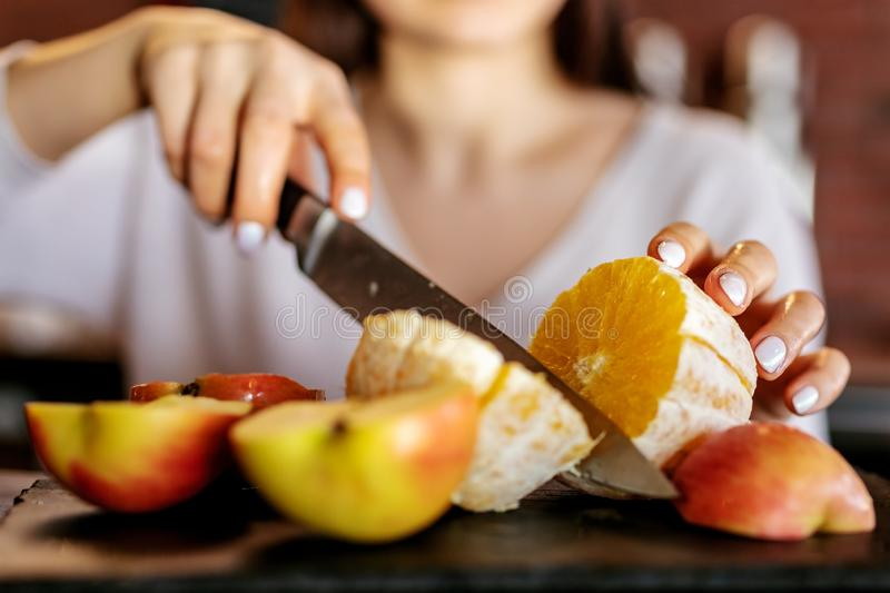 The girl cut the orange with a knife royalty free stock images