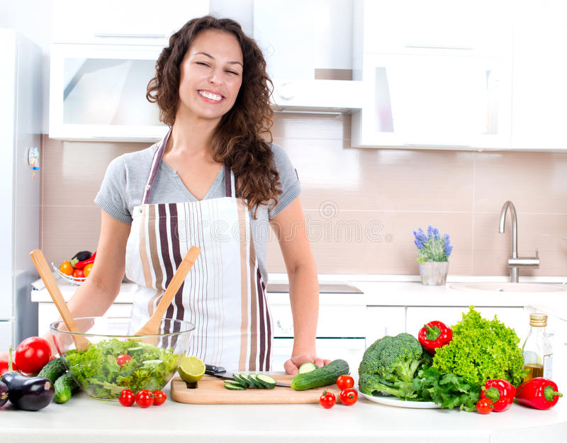 Young Woman Cooking. Healthy Food - Vegetable Salad royalty free stock images