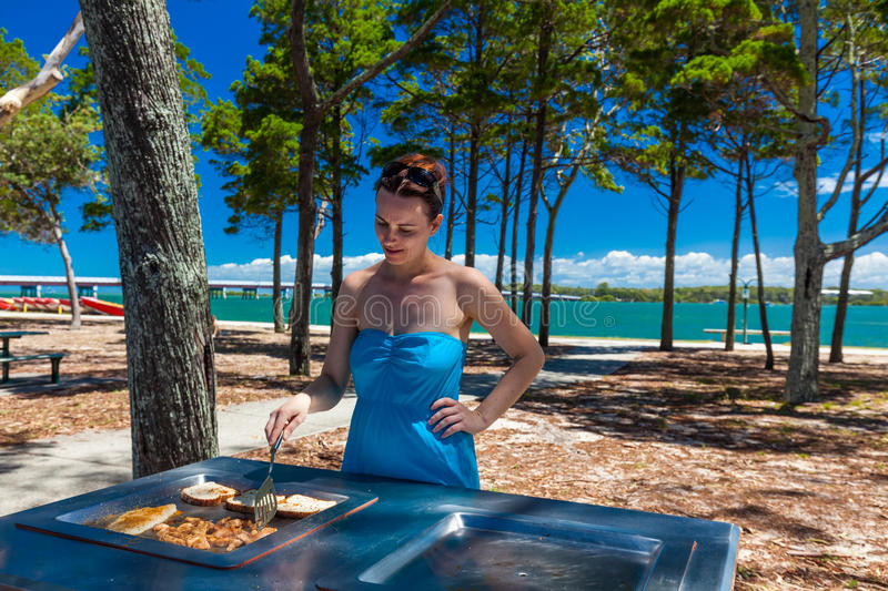 Young woman cooking barbeque on the beach in Australia stock photo