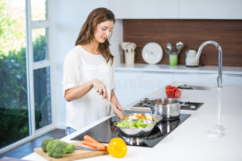 Young woman cooking food stock photo