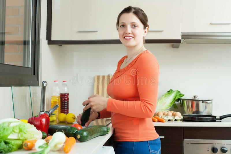 Young woman cooking fresh vegetables. In home kitchen royalty free stock image