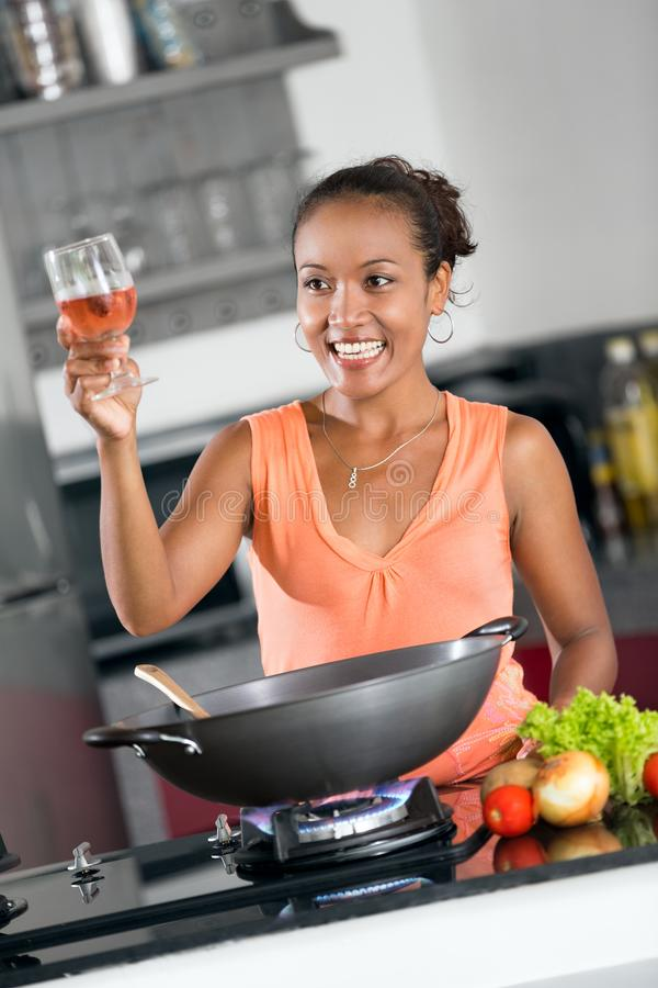 Young woman cooking for friends stock photo
