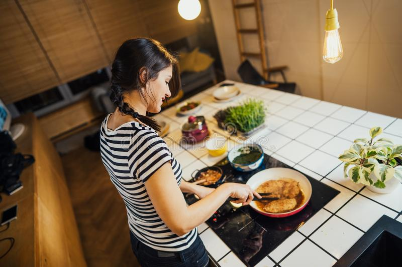 Young woman cooking a healthy meal in home kitchen.Making dinner on kitchen island standing by induction hob.Preparing fresh. Vegetables,enjoying spice aromas royalty free stock photos