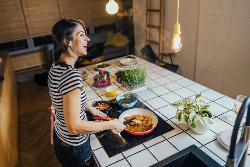 Young woman cooking a healthy meal in home kitchen.Making dinner on kitchen island standing by induction hob.Preparing fresh. Vegetables,enjoying spice aromas royalty free stock photography
