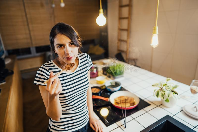 Young woman cooking a healthy meal in home kitchen.Making dinner on kitchen island standing by induction hob.Preparing fresh. Vegetables,enjoying spice aromas stock photo