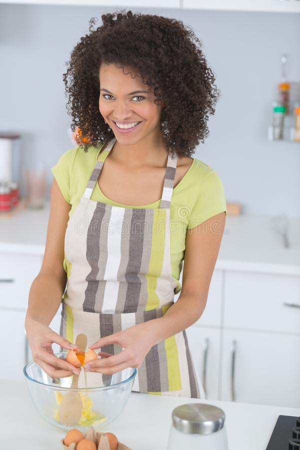 Young woman cooking in kitchen breaking eggs. Young royalty free stock images