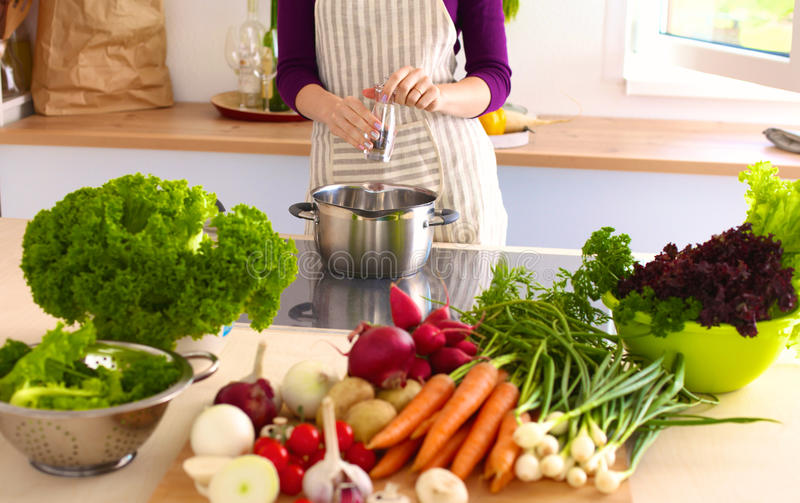 Young Woman Cooking in the kitchen. Healthy Food.  royalty free stock photography