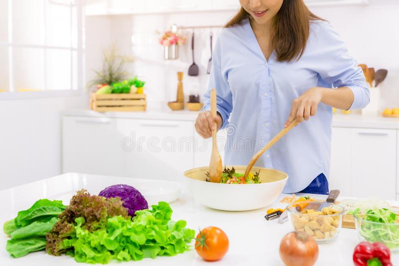 Young Woman Cooking in the kitchen. Healthy Food - Vegetable Salad. Diet. Dieting Concept. Healthy Lifestyle. Cooking At Home. stock photography