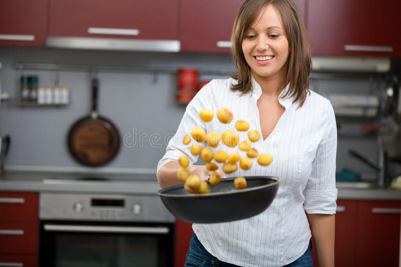 Young woman cooking potatoes in the kitchen stock photos