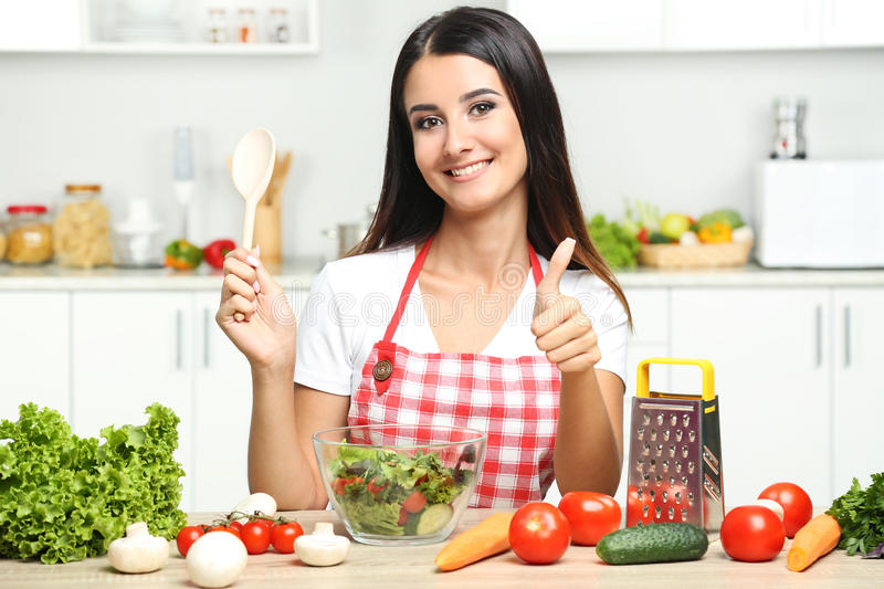 Young woman cooking salad. Beautiful young woman cooking salad in the kitchen stock photo