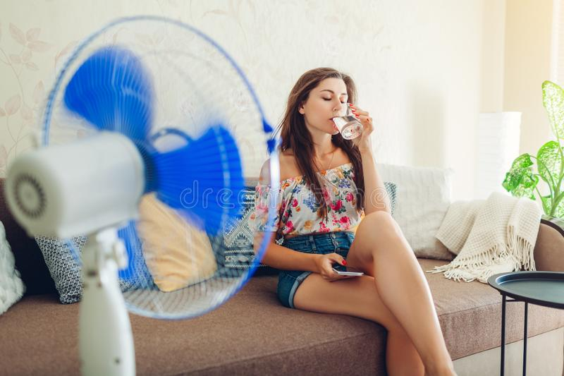 Young woman cooling down by ventilator at home while drinking water and hanging in phone. Summer heat. royalty free stock photography