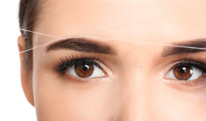 Young woman correcting eyebrow shape with thread,. Closeup stock photos