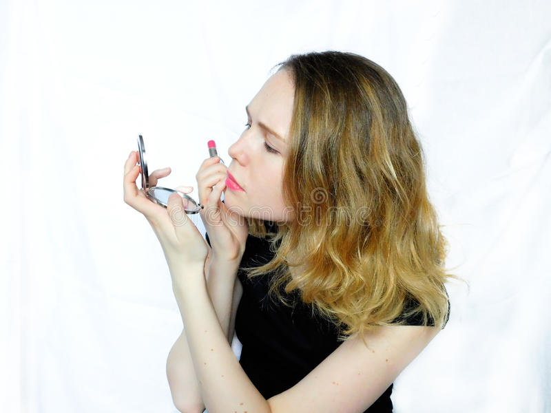 A young woman is correcting make-up royalty free stock photography