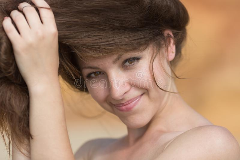 Young woman corrects her hairstyle and looking at camera smiling royalty free stock photos