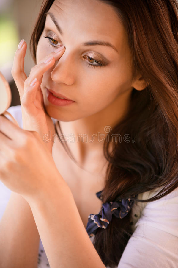 Download Young Woman Corrects Make-up Stock Photo - Image of green, casual: 14236500