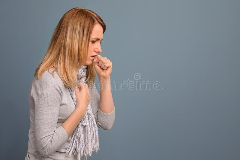 Young woman coughing. On color background stock image