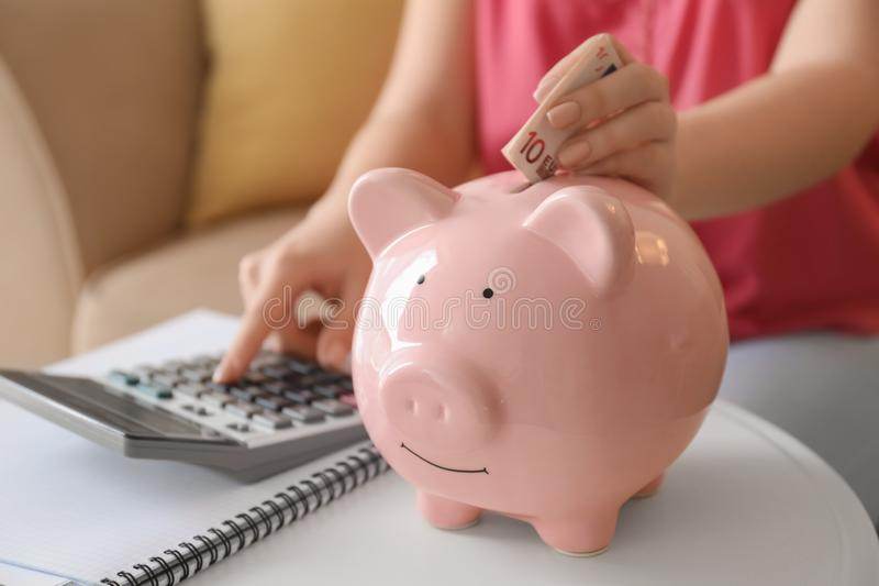 Young woman counting on calculator and putting euro banknote into piggy bank indoors, closeup. Money savings concept stock images