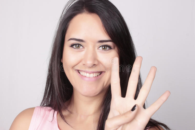 Young woman counting four with her fingers. Young beatiful caucasian woman counting four over white background. Hand counting, four fingers stock images