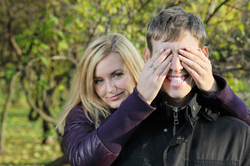 Young woman covered eyes of smiling man by hands royalty free stock photos