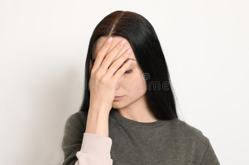 Young woman covering face against white. Background royalty free stock photography
