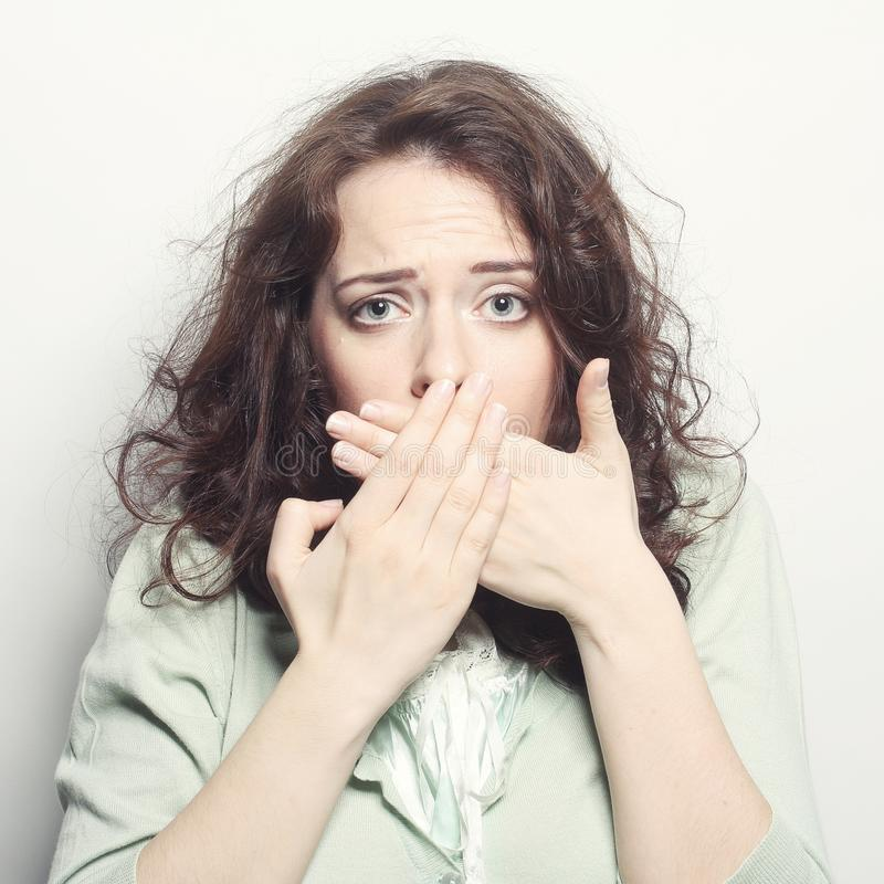 Young woman covering the face with her hand. Beautiful young woman covering the face with her hand stock image