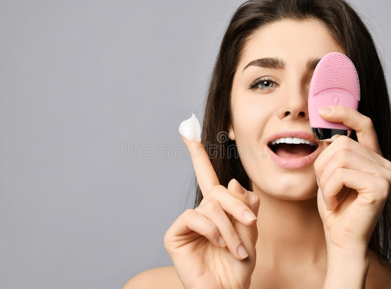 Young woman covers her eye with pink face brush silicone cleansing device for skin, shows cream on finger and smiles happily. Background. Text space royalty free stock image