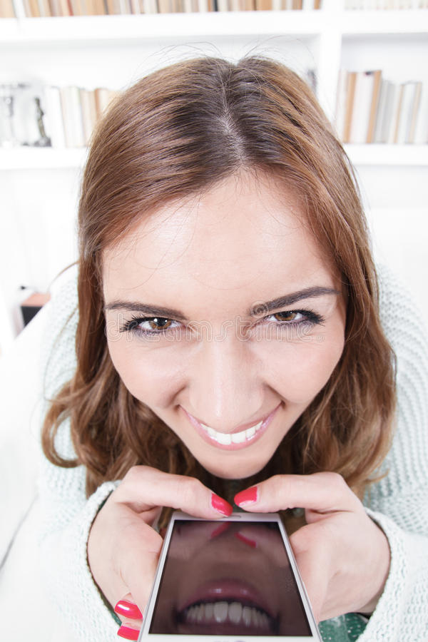 Young woman with crazy face expression. Is trying to spite insidiously with a mobile phone via a message or call, illegal apps for android or windows mobile royalty free stock photography