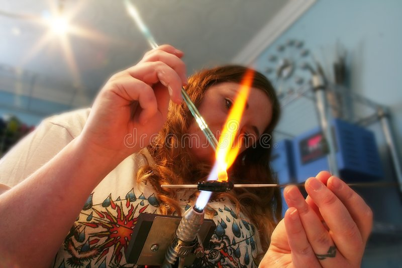 A young woman creates glass beads with heat. An artisan intently focused on her work stock images