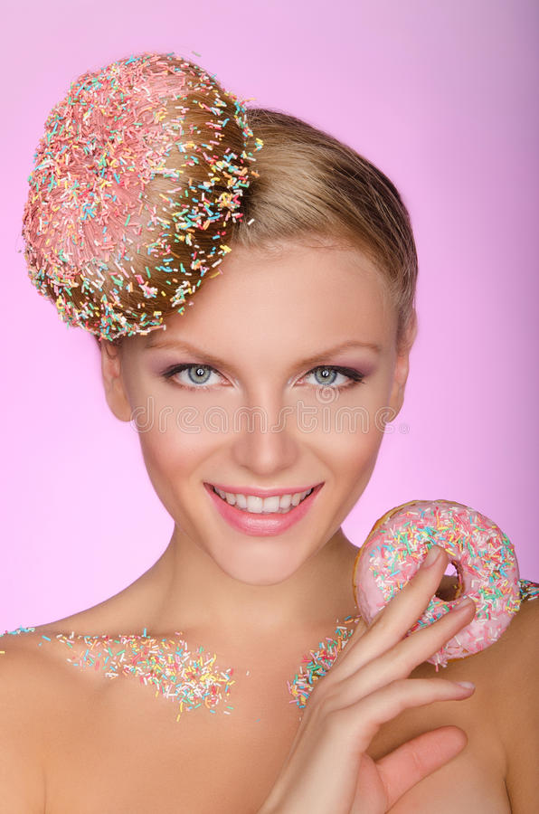 Young woman with creative hairstyle from donut. On pink background stock photography