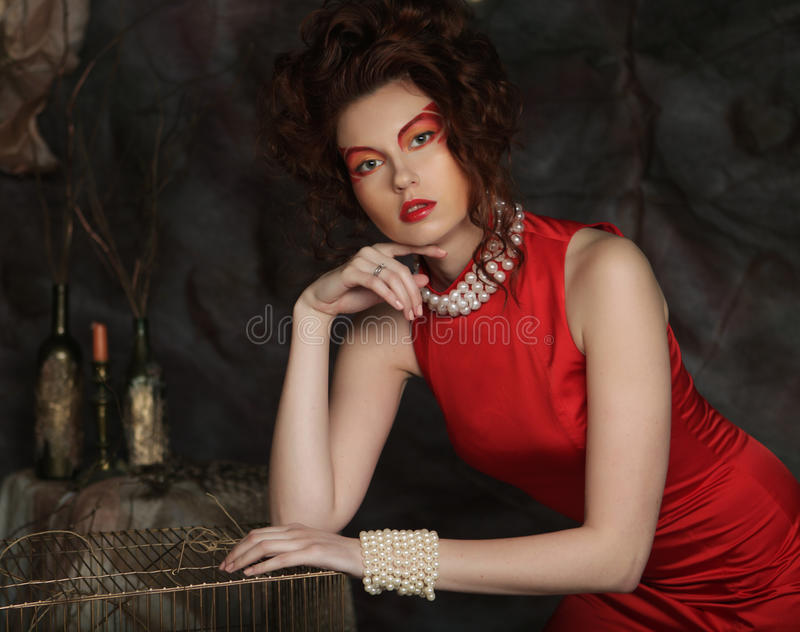 Young woman with creative visage wearing red dress stock photography