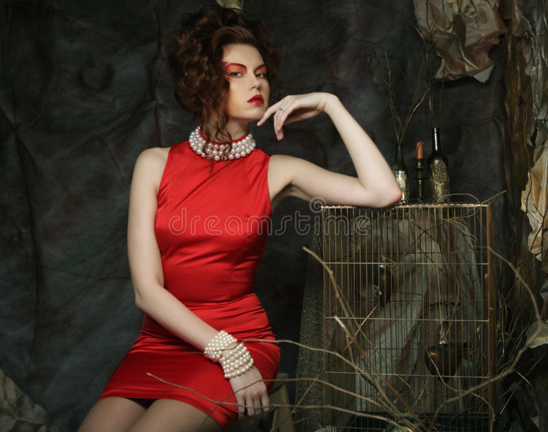 Young woman with creative visage wearing red dress stock image