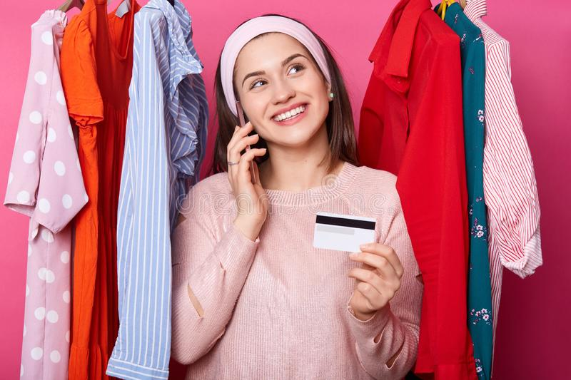 Young woman with credit card dreams about shopping while standing near lots hangers with colourful clothes isolated over pink royalty free stock images