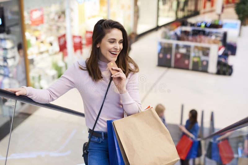 Young woman with credit card and full shopping bags stock photography