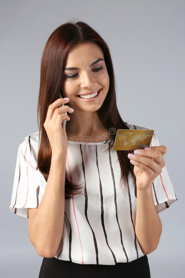 Young woman with credit card talking on mobile phone against grey background. Online shopping stock images