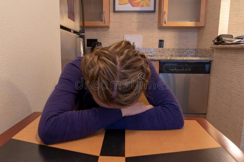 Young woman cries and buries her head and face in her arms while sitting at a kitchen table alone.  stock photo