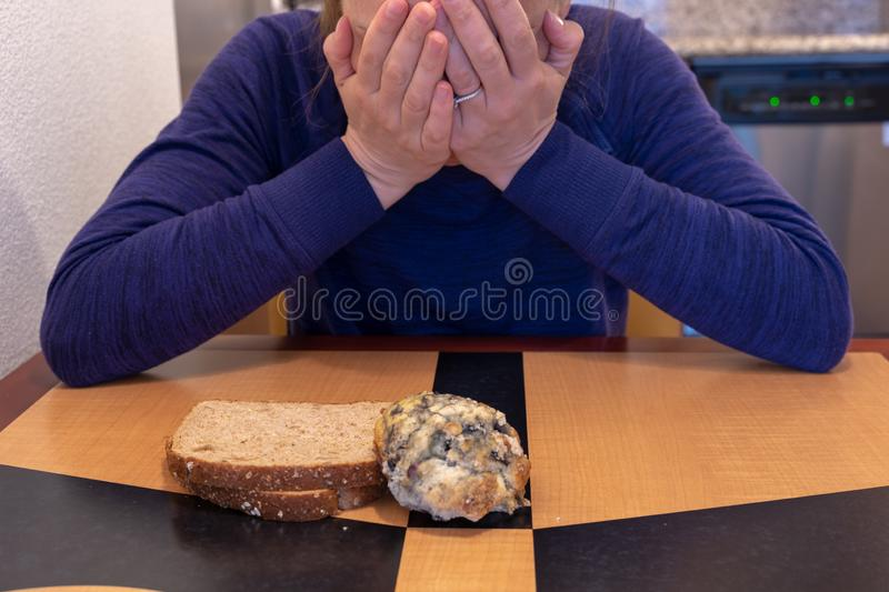 Young woman cries and buries her head and face while sitting at a kitchen table with a scone and toast. Concept for dieting and stock images