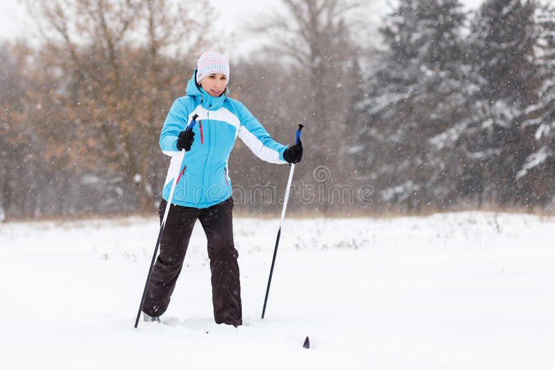 Young woman cross-country skiing in winter park stock image