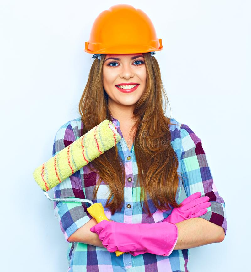 Young woman with crossed arms holding painting roller stock photography
