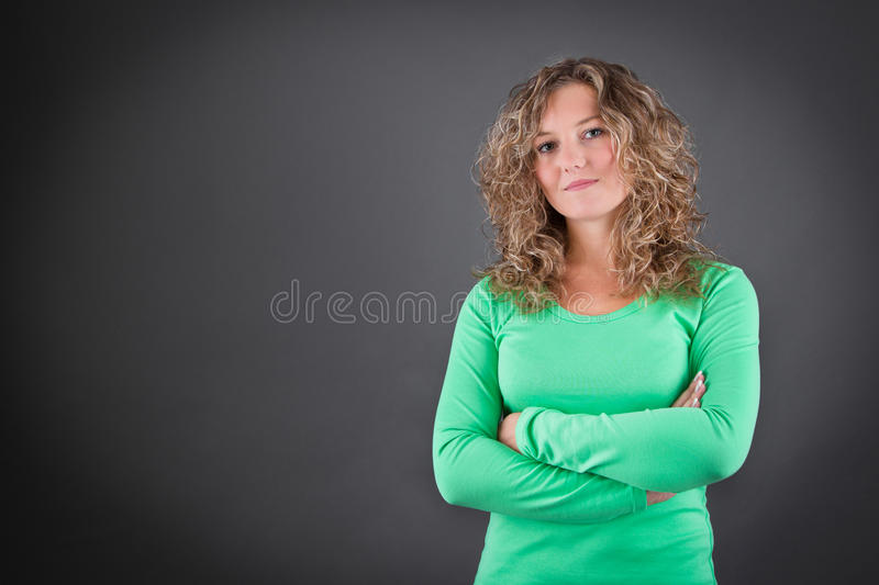 Young woman with crossed arms isolated on gray background royalty free stock photo