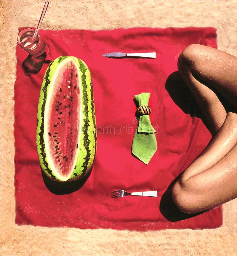 YOUNG WOMAN CROSSED LEGS SITTING ON SAND RED TABLECLOTH RED AND GREEN WATERMELON NAPKIN. Young woman sitting with crossed legs on sand facing red tablecloth with royalty free stock photography